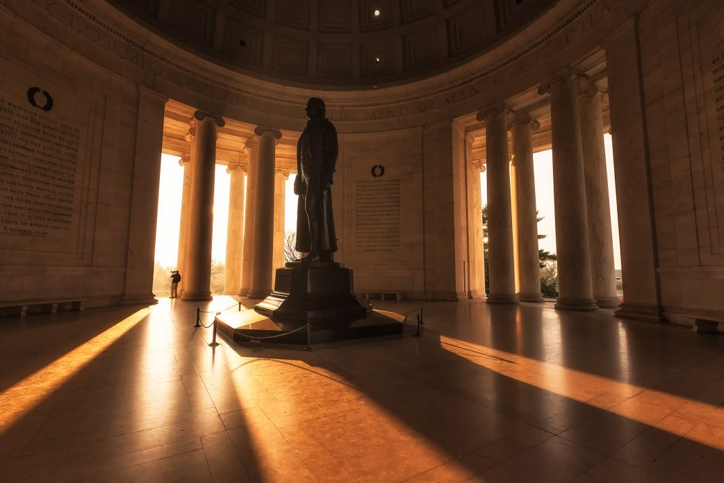 Golden, morning light streams through a mostly-empty Jefferson Memorial.