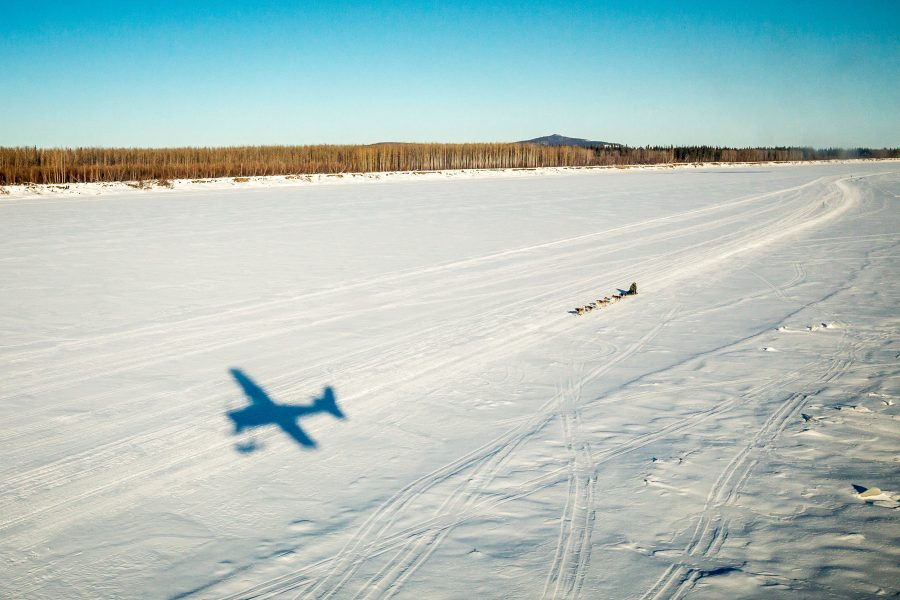 A sled dog team mushes along a frozen river, seen from a small airplane