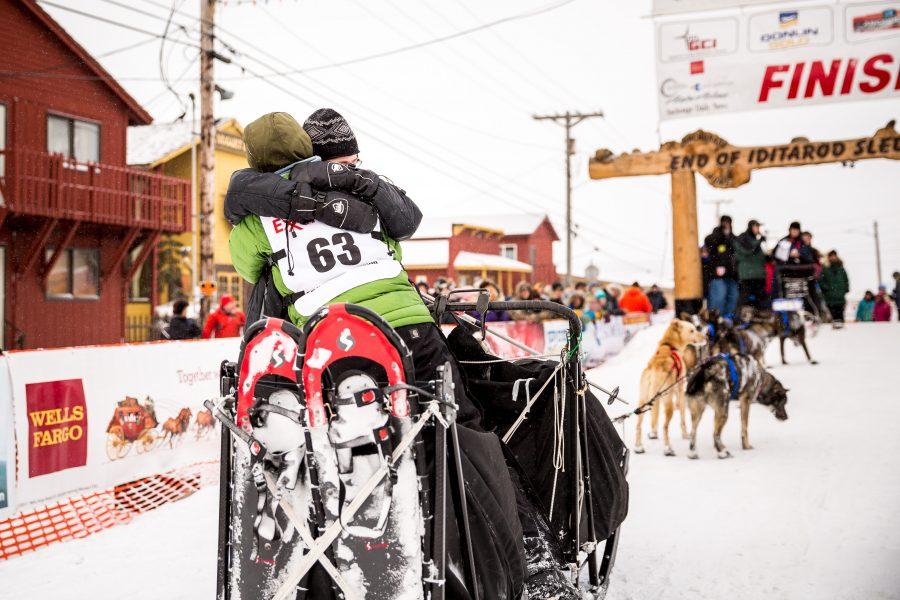 Sled dog musher hugs child at Iditarod finish line