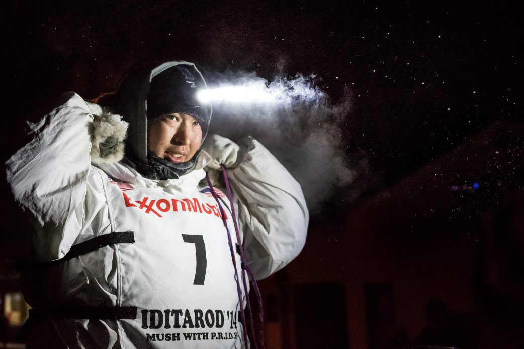 Iditarod musher in parka with snow falling around him at night
