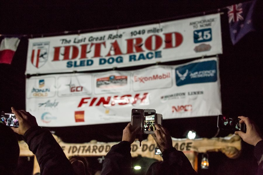 People holding up smartphone cameras to the Iditarod Finish sign.